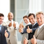 Successful business colleagues showing thumbs up sign